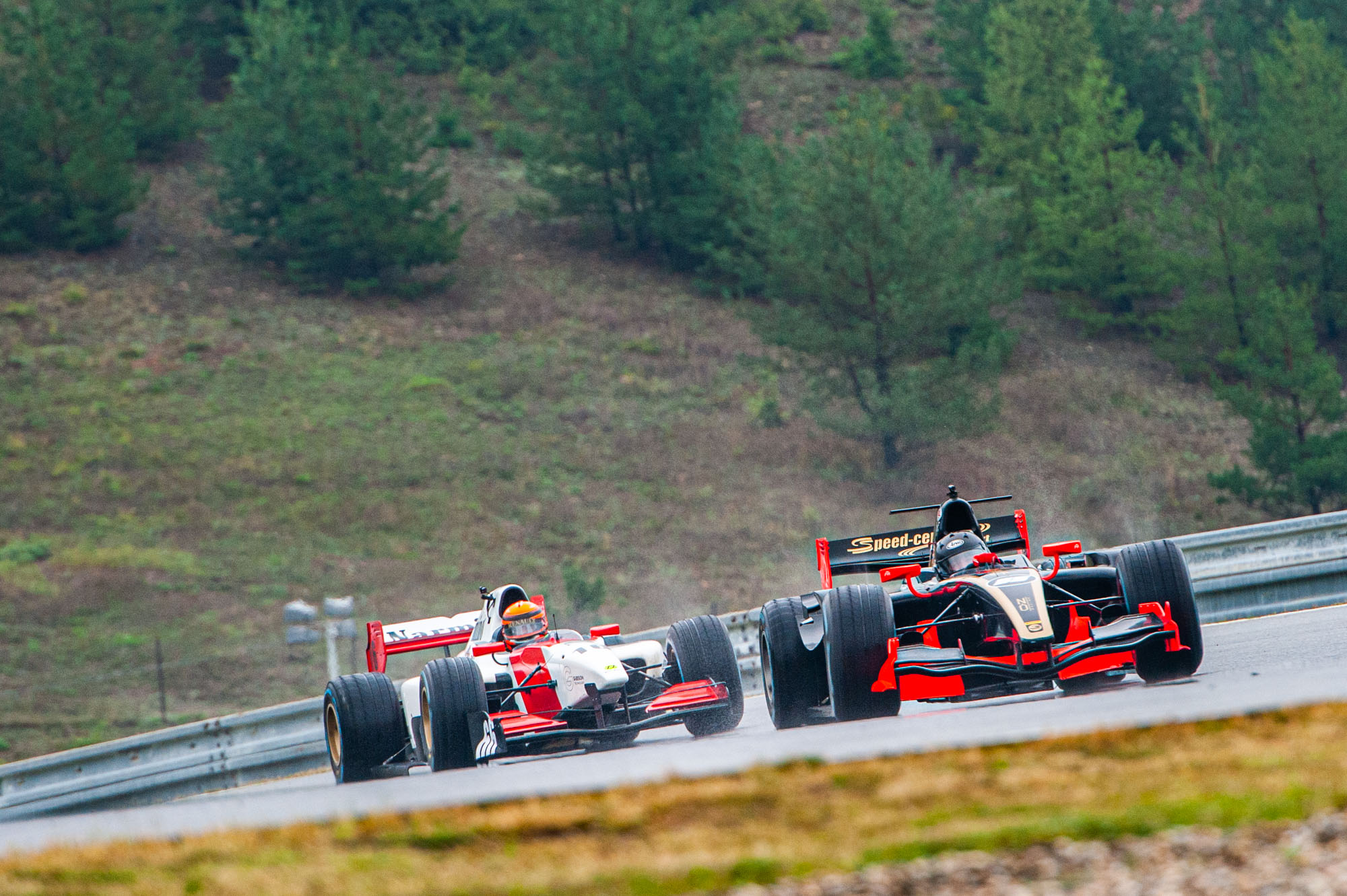 Two BOSS GP cars on wet weather tyres on a slippery track in Brno 2019